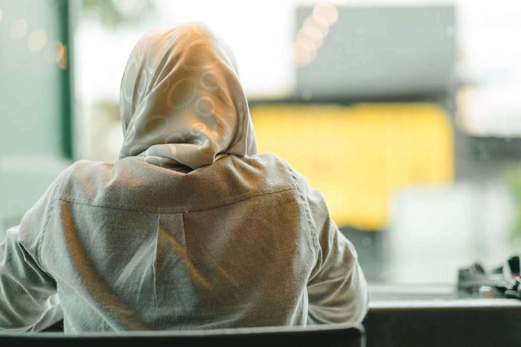 EARS - Veiled woman seen from the back